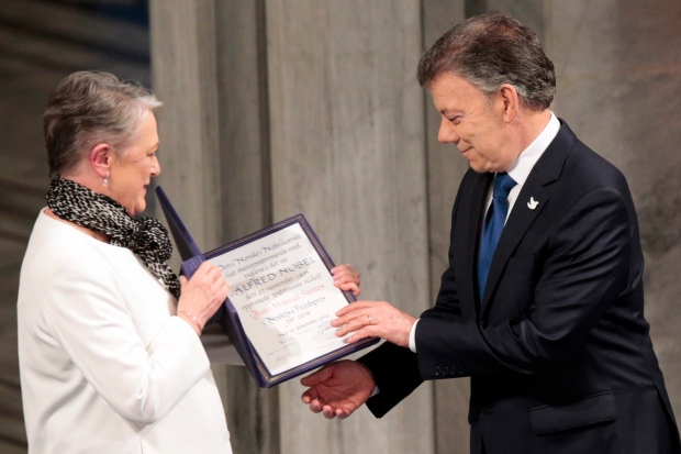 Nobel Peace Prize Laureate Colombian President Juan Manuel Santos receives the medal and diploma from Norwegian Nobel Committee member Berit Reiss-Andersen during the Peace Prize awarding ceremony at the City Hall in Oslo, Saturday Dec. 10, 2016. (Lise Aaserud / NTB scanpix)