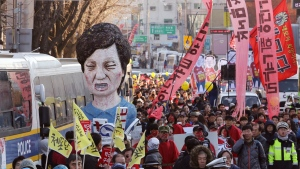 Protesters carry an effigy of impeached South Korean President Park Geun-hye as they march toward the presidential house during a rally in Seoul Saturday, Dec. 10, 2016. (AP Photo/Ahn Young-joon)