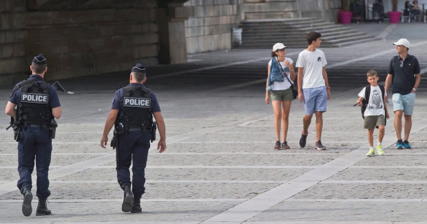 French Police officers patrol along the Seine river as a group of tourists pass by in Paris, France, Friday, Sept. 2, 2016. (AP / Michel Euler)