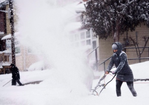 In this February 2, 2015 file photo, people clear snow from their sidewalks and streets after a large amount of snow fell in Toronto. (Nathan Denette / THE CANADIAN PRESS)