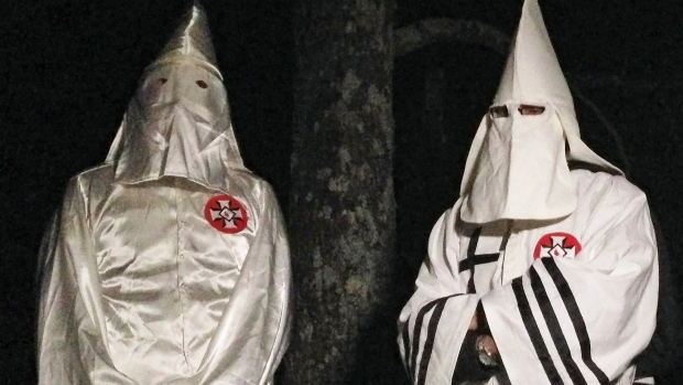 In this Friday, Dec. 2, 2016 photo, two masked Ku Klux Klansmen stand on a muddy dirt road during an interview near Pelham, N.C. (Jay Reeves/AP Photo)