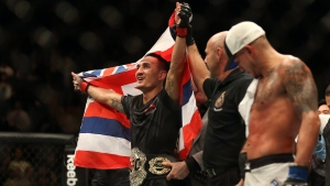 Max Holloway celebrates after defeating Anthony Pettis, right, to win the interim featherweight title during the main event of UFC 206 at the Air Canada Centre in Toronto, Ont., on Saturday, December 10, 2016. (THE CANADIAN PRESS/Peter Power)