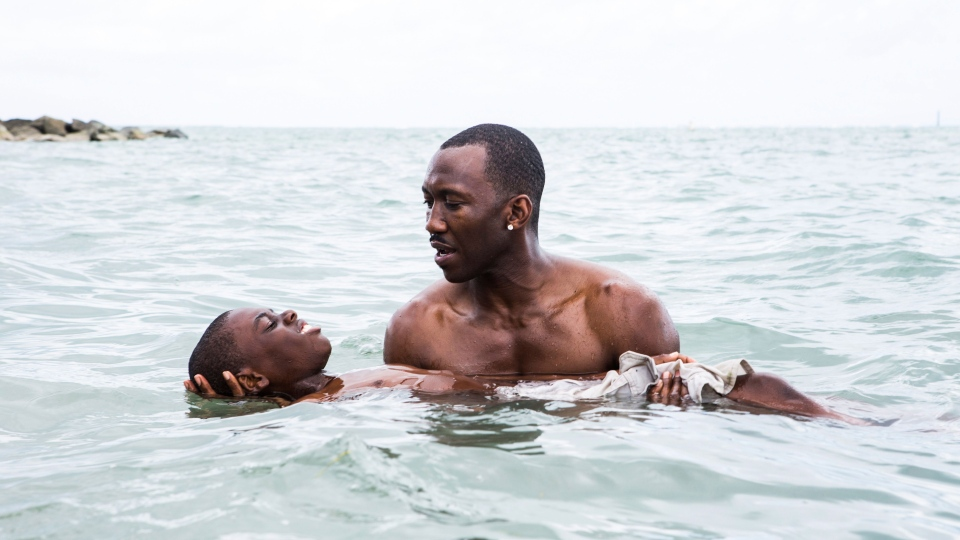 "This image released by A24 shows Alex Hibbert, foreground, and Mahershala Ali in a scene from the film, ""Moonlight."" The film was nominated for a Golden Globe award for best motion picture drama on Monday, Dec. 12, 2016. The 74th Golden Globe Awards ceremony will be broadcast on Jan. 8, on NBC. (David Bornfriend/A24 via AP)"