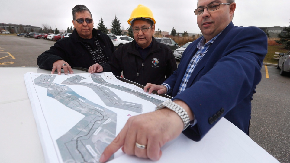 From left, Daryl Redsky, consultation officer, Chief Erwin Redsky, both of Shoal Lake 40 First Nation, and Phil Cesario, design project manager at PM Associates Ltd. go over the final design drawings for Freedom Road, an all-weather road which will connect the reserve to the Trans Canada highway. (John Woods / THE CANADIAN PRESS)