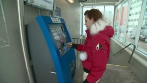 A woman pays to park at the MUHC hospital at the Glen (Dec. 12, 2016)