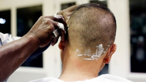 In this Feb. 27, 2015 photo, shop part-owner Wendell Patterson gets his hair cut by Mack McClellan, inside Taylor's Barber Shop, on Main Street in Marion, S.C. The barber shop recently marked its 100th anniversary of being in business. (AP Photo/The Morning News, Veasey Conway)