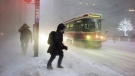 A person makes their way to a streetcar as snow flies through the air during a squall in downtown Toronto, on Thursday, December 15, 2016. (THE CANADIAN PRESS/Graeme Roy)