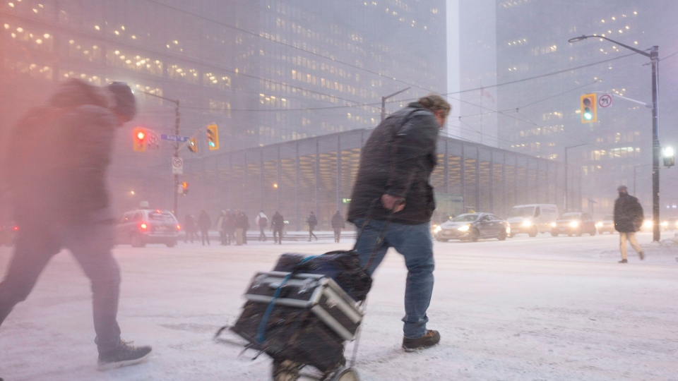 A person makes their way across King Street as snow flies through the air during a squall in downtown Toronto's financial district, on Thursday, December 15, 2016. THE CANADIAN PRESS/Graeme Roy
