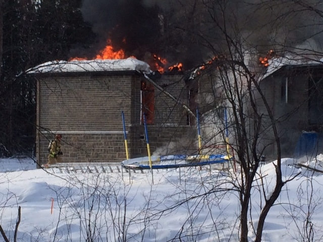 Flames are seen tearing through the roof of a home on Hedley Way in Kanata on Friday, Dec. 16, 2016.