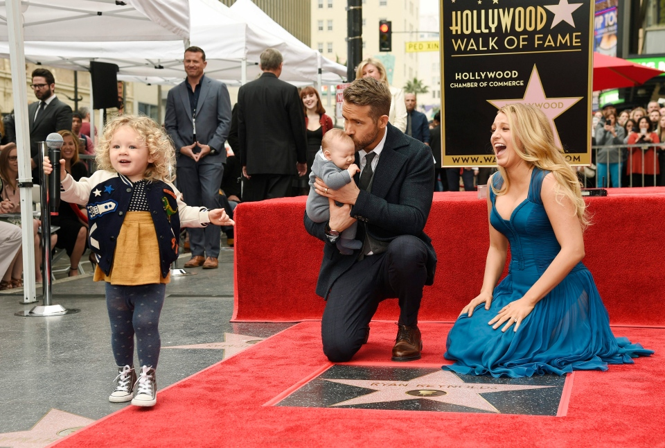Ryan Reynolds' daughter James, left, steals the microphone as Reynolds poses with his wife, actress Blake Lively, and their youngest daughter during a ceremony to award him a star on the Hollywood Walk of Fame in Los Angeles on Thursday, Dec. 15, 2016. (Chris Pizzello / Invision)