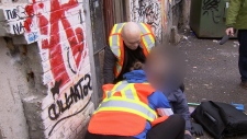 Volunteers work to help a drug user after a suspected fentanyl overdose in Vancouver's Downtown Eastside neighbourhood. (CTV)