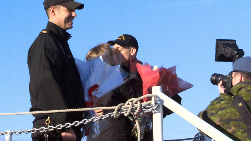 A sailor and his girlfriend take part in the first-kiss tradition after HMCS Brandon and HMCS Edmonton returned to a Canadian Armed Forces base in Esquimalt, B.C. Fri., Dec. 16, 2016. (CTV Vancouver Island)