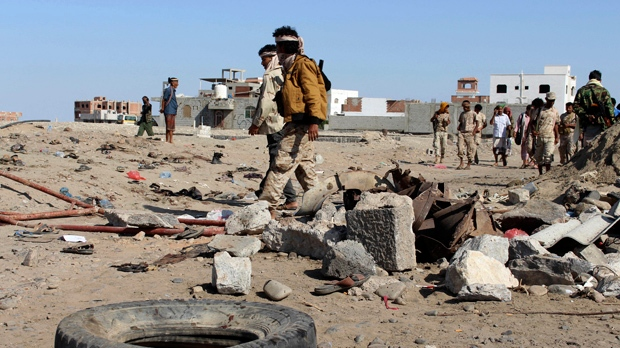Soldiers gather the site of a suicide bomb at a base in the southern city of Aden, Yemen, Sunday, Dec. 18, 2016. (AP Photo/Wael Qubady)
