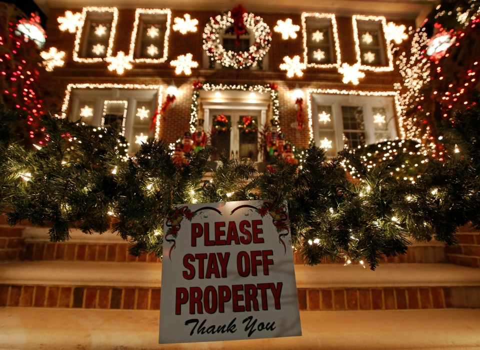 In this Dec. 14, 2016, photo, a sign in front of a decorated house warns visitors to keep off the premises in the Dyker Heights neighbourhood of New York. (AP Photo/Kathy Willens)