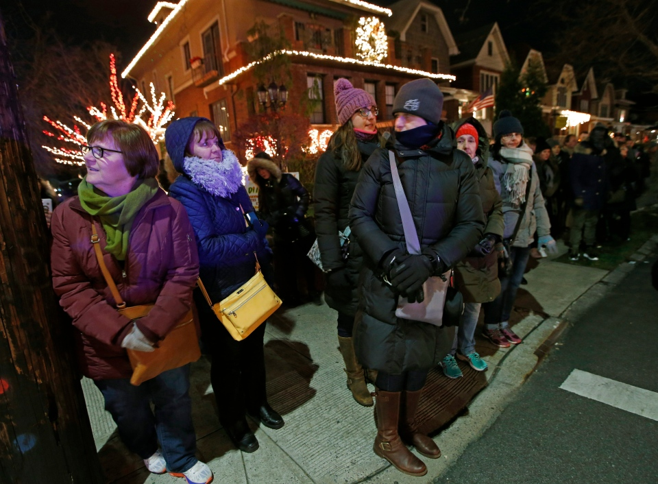 In this Dec. 14, 2016, photo, bundled-up tourists from a 'Tour America' group glance around the Dyker Heights neighborhood in Brooklyn Borough of New York after arriving by giant tour bus from midtown Manhattan. (AP Photo/Kathy Willens)
