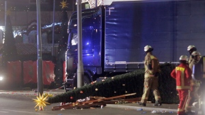 Firefighters stand beside a truck which ran into a crowded Christmas market and killed several people in Berlin, Germany, Monday, Dec. 19, 2016. (Markus Schreiber/AP Photo)
