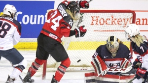 Canada's Natalie Spooner watches Marie-Philip Poulin's shot go in behind USA goalie Nicole Hensley during overtime action in an exhibition game in between the Women's National teams in Sarnia, Ont., on Monday, Dec. 19, 2016. (Dave Chidley/The Canadian Press)