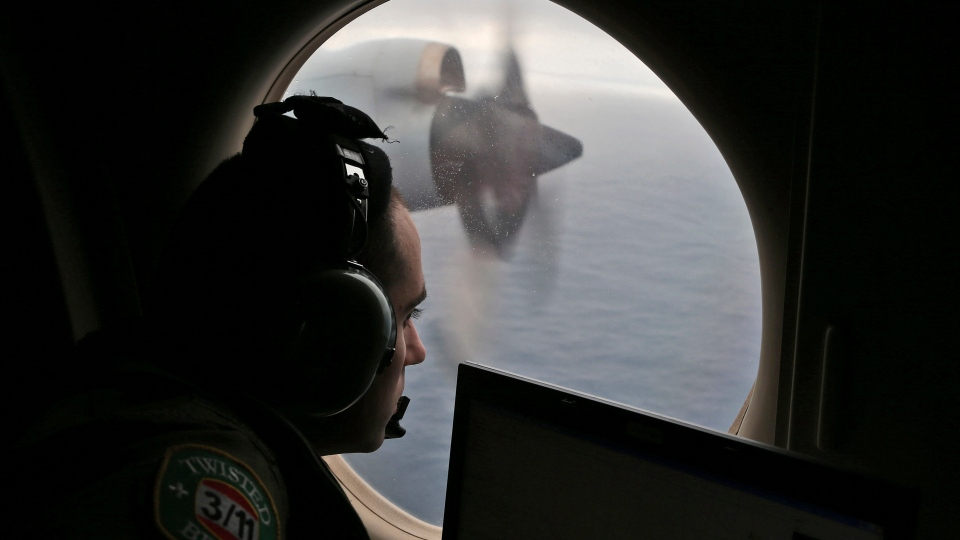 FILE - In this March 22, 2014 file photo, flight officer Rayan Gharazeddine scans the water in the southern Indian Ocean off Australia from a Royal Australian Air Force AP-3C Orion during a search for the missing Malaysia Airlines Flight MH370. (AP Photo/Rob Griffith, File)