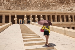 A tourist shelters from the sun under an umbrella at the ancient temple of Hatshepsut, on the west bank of the Nile River, in Luxor, 510 kilometres (320 miles) south of Cairo, Egypt, Saturday, May 2, 2015. (AP Photo/Mosa'ab Elshamy)