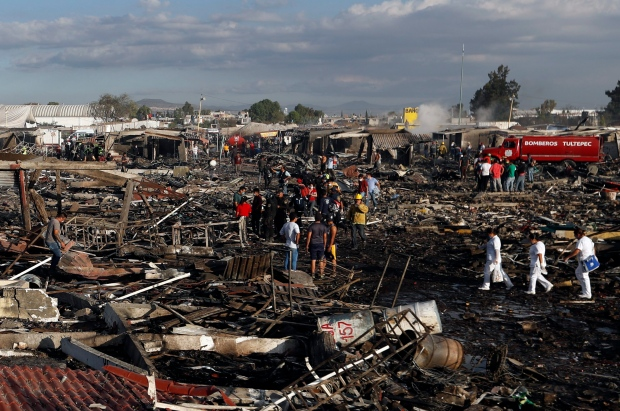 Firefighters and rescue workers walk through the scorched ground of Mexico's best-known fireworks market after an explosion explosion ripped through it, inTultepec, Mexico, Tuesday, Dec. 20, 2016. (AP / Eduardo Verdugo)