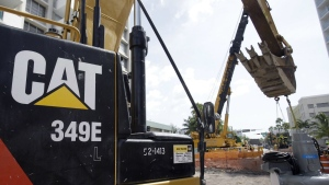 A Caterpillar 349E Hydraulic Excavator operates on a construction site in Miami Beach, Fla. on Wednesday, Sept. 17, 2014. (AP / Wilfredo Lee)