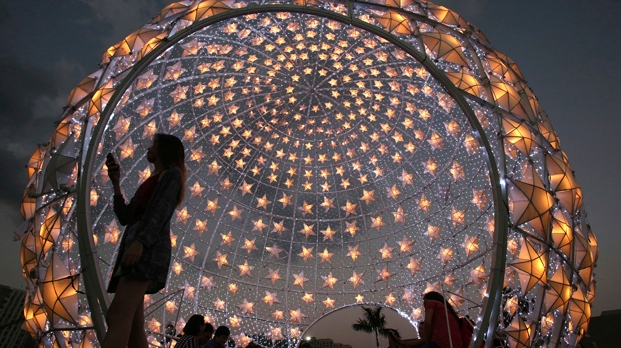 A woman walks past a lit Christmas display at a park in Pasay, south of Manila, Philippines on Thursday, Dec. 22, 2016. (AP Photo/Aaron Favila)