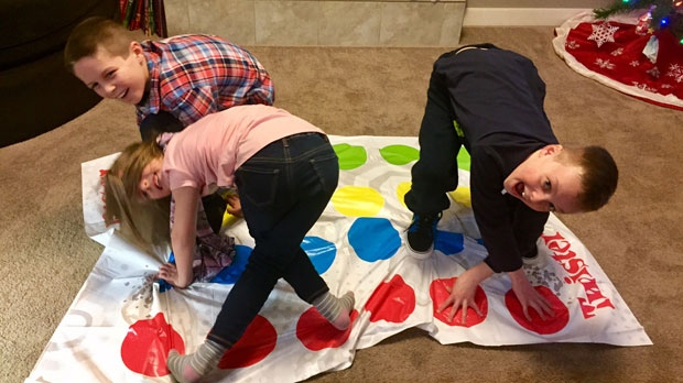 Ethan Nielson (right) plays a game of Twister with his brother Skyler and sister Rylee.