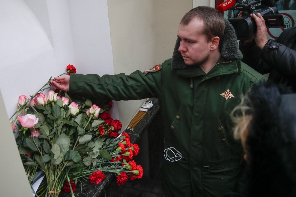 Alexander, a former member of the Alexandrov Ensemble, a well-known military choir, lays flowers at the military choir's building in Moscow, Russia, Sunday, Dec. 25, 2016, after a plane carrying 64 members of the Alexandrov Ensemble, crashed into the Black Sea minutes after taking off from the resort city of Sochi. (AP / Pavel Golovkin)