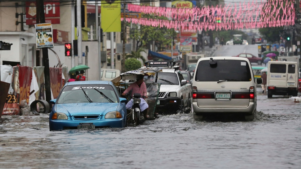 Vehicles navigate a flood-prone area caused by rains from Typhoon Nock-Ten in Quezon city, north of Manila, Philippines on Monday, Dec. 26, 2016. (AP Photo/Aaron Favila)
