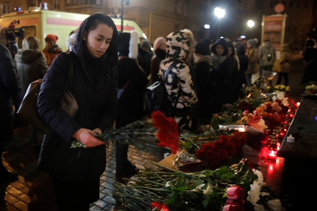 A woman lays flowers at the well-known military choir's building in Moscow, Russia, Sunday, Dec. 25, 2016, after a plane carrying 92 people, with 64 members of the Alexandrov Ensemble, crashed into the Black Sea minutes after taking off from the resort city of Sochi. The Russian plane was headed for an air base in Syria, Russia's Defense Ministry said. (AP Photo/Pavel Golovkin)