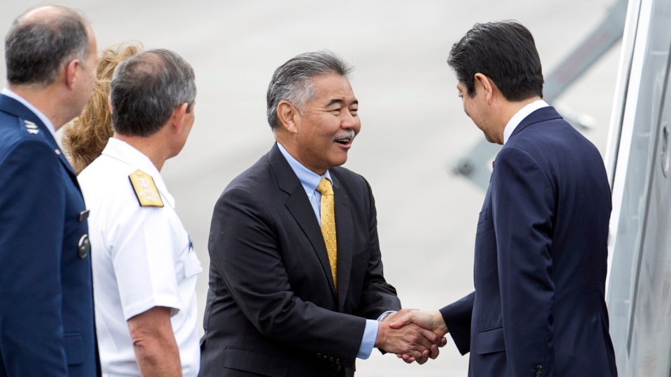 Hawaii Gov. David Ige, center, greets Japanese Prime Minister Shinzo Abe at Joint Base Pearl Harbor Hickam, Monday, Dec. 26, 2016, in Honolulu. Abe will visit Pearl Harbor with U.S. President Barack Obama on Tuesday, becoming the first leader of Japan to visit Pearl Harbor, the site of the surprise attack that propelled the United States into World War II. 2016 marks the 75th anniversary of the Japanese attack. (AP/Marco Garcia)