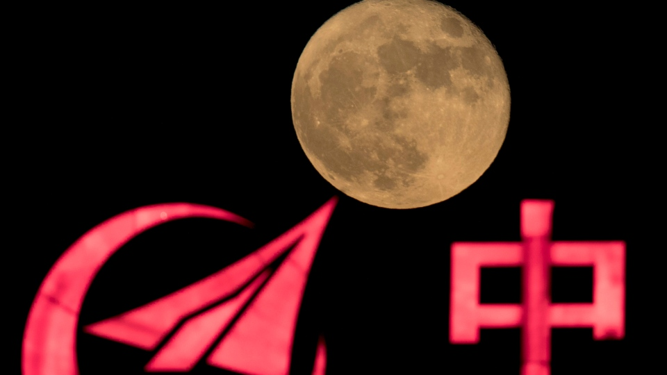 In this photo taken Tuesday, Nov. 15, 2016, the supermoon rises over a logo for AVIC, or Aviation Industry Corp, a state owned enterprise involved in China's manned space mission in Beijing.  (AP/Ng Han Guan)