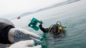 A Russian Emergency Ministry diver lifts a fragment of a plane in the Black Sea, outside Sochi, Russia, on Dec. 27, 2016. (Viktor Klyushin / AP)