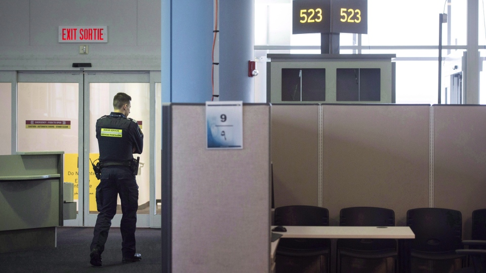 FILE - A Canadian Border Services agent stands watch at gate at Pearson International Airport in Toronto on Tuesday, December 8, 2015. (THE CANADIAN PRESS/Darren Calabrese)