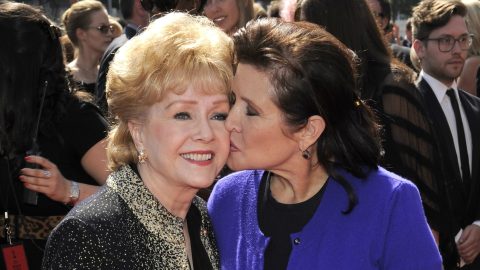 In this Sept. 10, 2011, file photo, Debbie Reynolds, left, and Carrie Fisher arrive at the Primetime Creative Arts Emmy Awards in Los Angeles. (AP / Chris Pizzello)