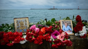 An icon and a portrait of Yelizaveta Glinka are placed among flowers at a pier in Sochi, Russia, in Sochi, Russia, on Dec. 28, 2016. (Viktor Klyushin / AP)