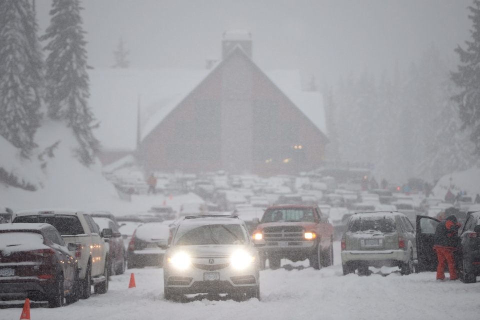Vehicles make their way through heavy snow at the Cypress Mountain ski resort in West Vancouver, Thursday, Dec.29, 2016. (Jonathan Hayward / THE CANADIAN PRESS)