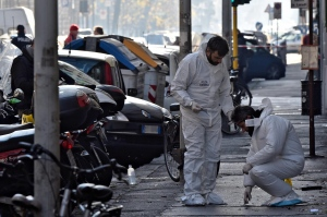 Forensic police collect evidence on the site of the explosion of a bomb in front of a bookstore in Florence, Italy, Sunday, Jan. 1, 2017. (Maurizio Degl'Innocenti / ANSA via AP)