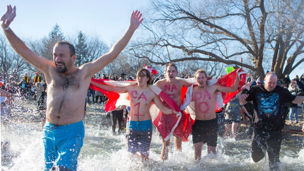Participants run into Lake Ontario as they take part in the Courage Polar Bear Dip in Oakville, Ont., on Sunday, January 1, 2017. THE CANADIAN PRESS/Chris Young