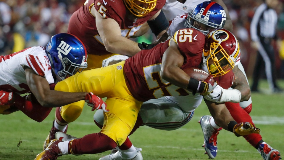 Washington Redskins running back Chris Thompson (25) is hauled to the ground by New York Giants cornerback Eli Apple (24) and outside linebacker Jonathan Casillas (52) during the second half of an NFL football game in Landover, Md., Sunday, Jan. 1, 2017. (AP / Alex Brandon)