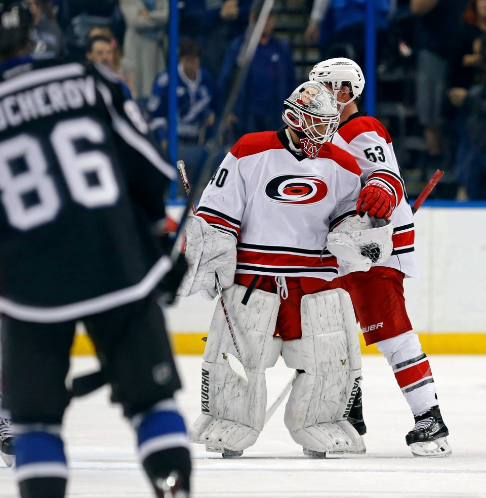 Carolina Hurricanes emergency backup goalie Jorge Alves is given the game puck by Jeff Skinner (53) following his NHL debut in the team's NHL hockey game against the Tampa Bay Lightning oni Saturday, Dec. 31, 2016, in Tampa, Fla. (Mike Carlson/AP Photo)