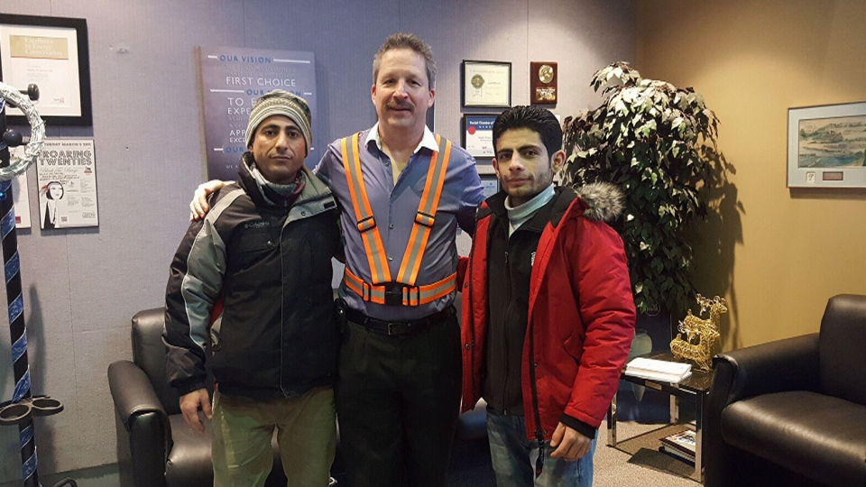 Jim Estill, centre, has sponsored more than 50 Syrian families in Canada.