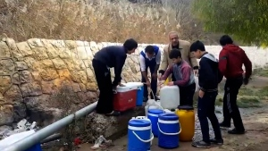 This frame grab from video provided By Yomyat Kzefeh Hawen Fi Dimashq (Diary of a Mortar Shell in Damascus), a Damascus-based media outlet that is consistent with independent AP reporting, shows Syrian residents filling up buckets and gallons of spring water from a pipe on the side of the road, in Damascus, Syria.  (Yomyat Kzefeh Hawen Fi Dimashq (Diary of a Mortar Shell in Damascus), via AP)
