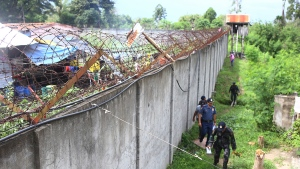 Policemen patrol outside the walls of the North Cotabato District Jail in Kidapawan city, Cotabato Province, southern Philippines, after a massive jailbreak early Wednesday, Jan. 4, 2017. (AP Photo)