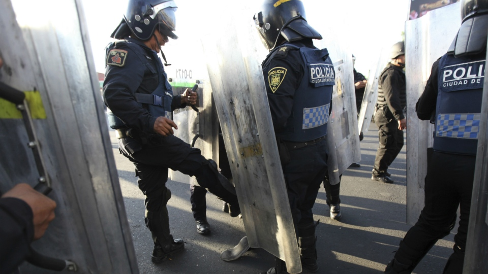 An officer kicks a demonstrator as police forcibly remove people who blocked a main road for about an hour, as part of protests against gas price hikes in Mexico City, Wednesday, Jan. 4, 2017. (AP / Marco Ugarte)