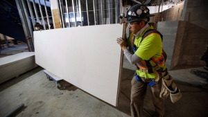 Construction workers move sheets of drywall at a building project in Calgary, Alta., on Dec. 30, 2016. (Jeff McIntosh / THE CANADIAN PRESS)