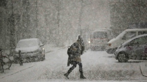 A person walks through a heavy snowfall during a day of winter weather in Berlin, Thursday, Jan. 5, 2017. (AP Photo/Markus Schreiber)