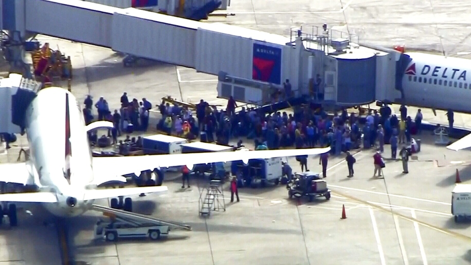 People stand on the tarmac after a shooting at Fort Lauderdale–Hollywood International Airport, in Fort Lauderdale, Fla, Friday, Jan. 6, 2017.
