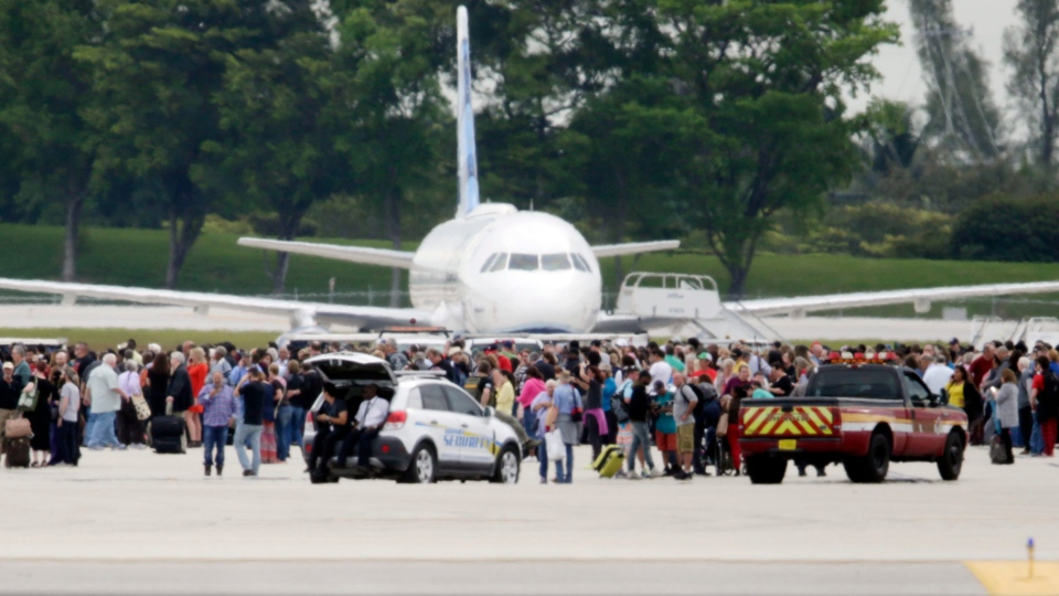 People stand on the tarmac at the Fort Lauderdale-Hollywood International Airport after a shooter opened fire inside a terminal of the airport, killing several people and wounding others before being taken into custody, Friday, Jan. 6, 2017, in Fort Lauderdale, Fla. (Lynne Sladky/AP Photo)