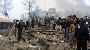 Rescue workers attend to the wreckage after they and Syria's opposition activists say dozens were killed when a car bomb went off in a busy market in a rebel-held Syrian town of Azaz along the Turkish border, Saturday, Jan. 7, 2017 . (Saif Alnajdi, via AP)